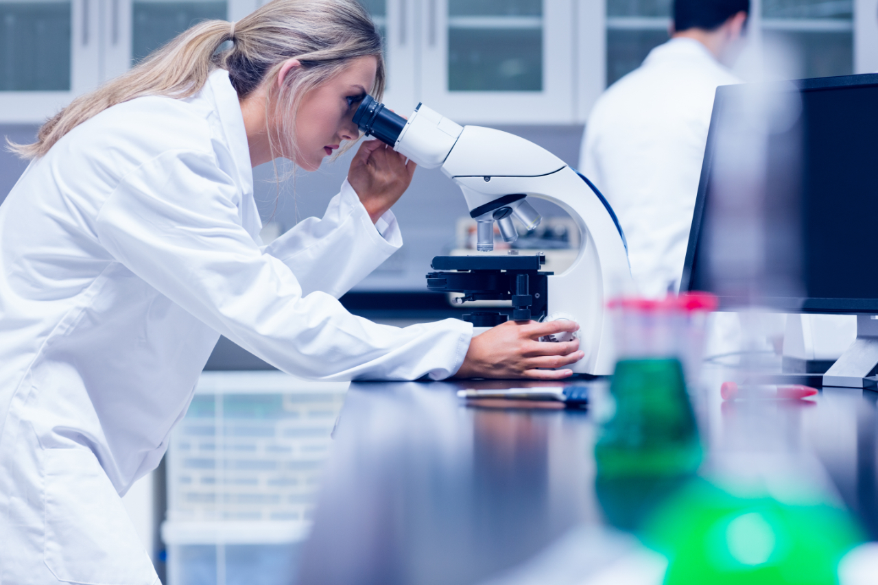 Nő éppen vizsgál valamit a laborban