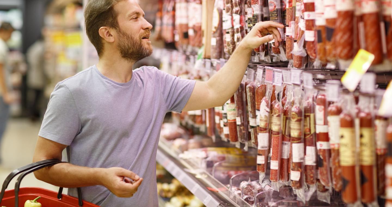 Csomagolt szalámik között válogató szürke pólós, fiatal férfi a szupermarketben