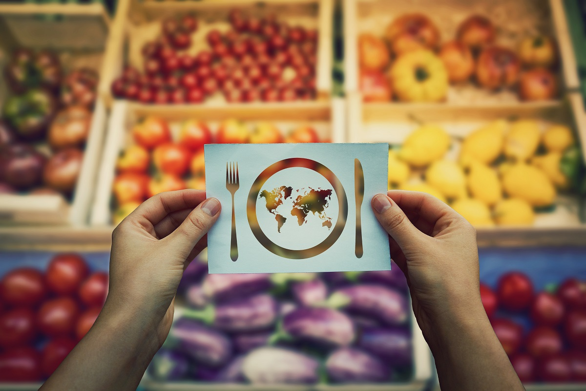Élelmiszereket ábrázoló kép, ami elé egy kivágott lap van tartva, ami egy földet ábrázoló tányért és evőeszközöket mutat