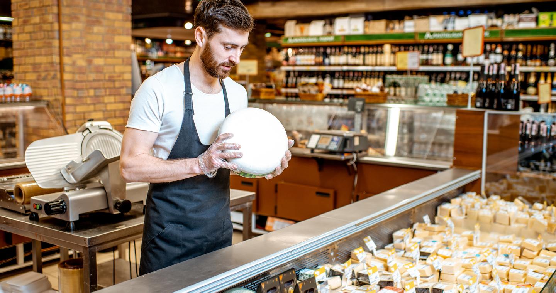 Szupermarket sajtpultjában sajtok között válogató férfi eladó
